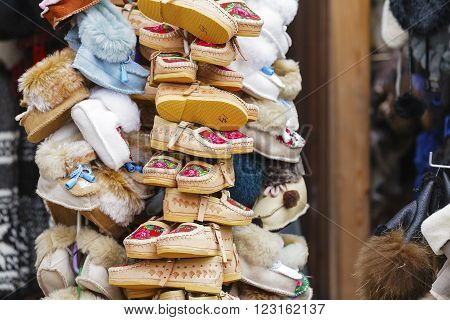 ZAKOPANE POLAND - MARCH 11 2016: Handmade footwear made of leather decorated with the local traditional way put on sale at the local market. These shoes are also used as popular gifts from Zakopane