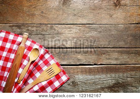Checkered napkin and cutlery on wooden background