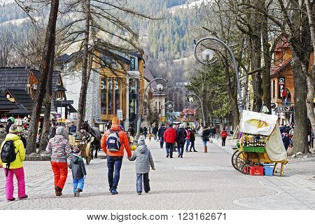 ZAKOPANE POLAND - MARCH 09 2016: Unidentified tourists visits Krupowki street the main shopping area and pedestrian promenade in the city