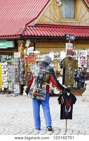 ZAKOPANE POLAND - MARCH 09 2016: Unrecognized man wears advertising banner in addition in hand holds the stick on which they are placed more promotional materials