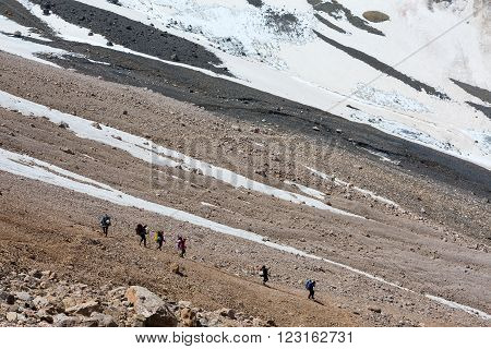 Six Members of Team Sport Clothing with Heavy Backpacks and Climbing Gear Going Down  Mountain Landscape with Moraine Snowfield and Glacier on Background