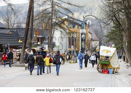 ZAKOPANE POLAND - MARCH 09 2016: Unrecognized passers are walking along Krupowki. It is main shopping area and pedestrian promenade in the downtown is very famous and frequently visited by tourists