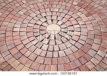 Patio bricks installation in circular pattern in sunny day