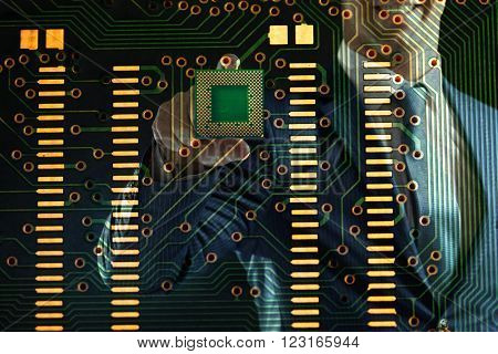 Man holding microchip and electronic circuit board, close up