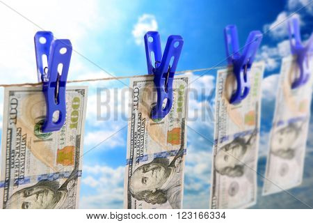 Concept of money laundering - dollars are drying on cord on sky background
