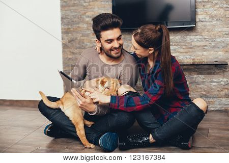 Happy couple with Shar Pei puppy surfing on the internet via digital tablet