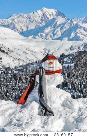 Snowman in a scarf and a a cap on a background of Mont Blanc