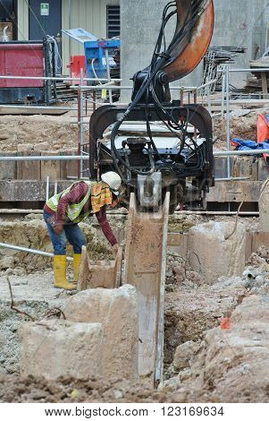 SELANGOR, MALAYSIA - MARCH 12, 2015: Sheet pile cofferdam driven machine at the construction site. This machine drove the sheet pile to the earth using vibrated hydraulic arm. Workers control.