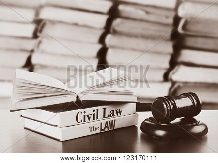 Wooden judges gavel and law books on table in library