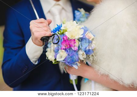 Bride and groom holding a bouquet of white, blue, red flowers. Groom in a blue suit, white tie, holding an umbrella. Bride holding a bouquet of hydrangea, freesia and tulip. Close-up. Focus on flowers.