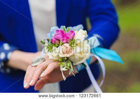 Bridesmaids holding a bouquet of white, blue, red flowers.  Bouquet of hydrangea, freesia and tulip on hand. Blue and white ribbon. Close-up. Focus on flowers.