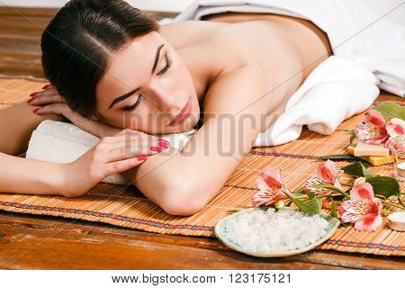 Beautiful young woman at a spa salon resting on a straw mat. Concept of body care and relaxation