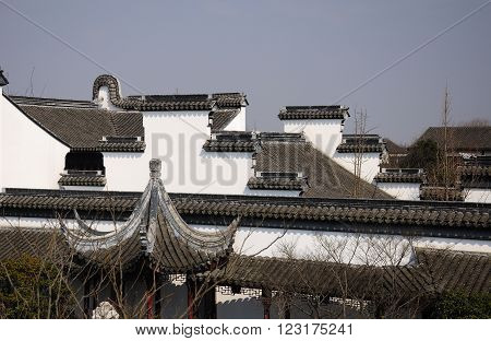 The white walls and rooftops of buildings at Li Yuan Garden in the water town of Zhaojialou in Shanghai China against a blue sky.