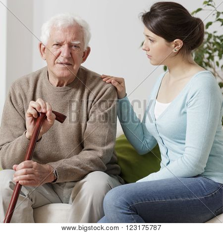 Elderly man with walking stick and with granddaughter