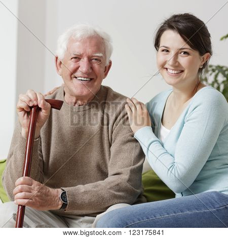 Smiling old man with his young granddaughter