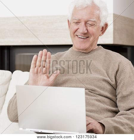 Old man using laptop to communicate with his family