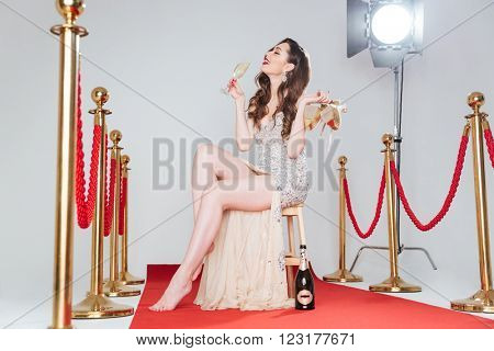 Happy charming woman holding heels and glass of champagne on red carpet