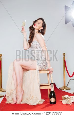 Charming famous woman sitting on the chair and holding glass with champagne on red carpet