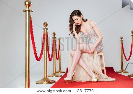 Beautiful woman in fashion dress sitting on the chair on red carpet