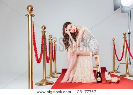 Charming woman holding glass with champagne on red carpet