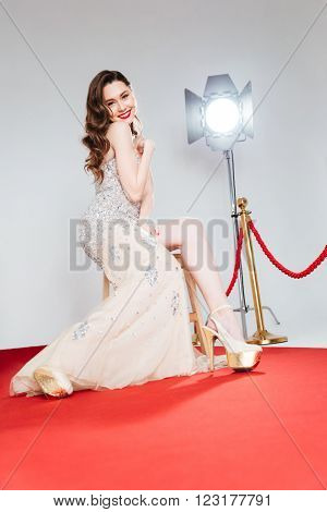 Full length portrait of a happy cute woman on red carpet