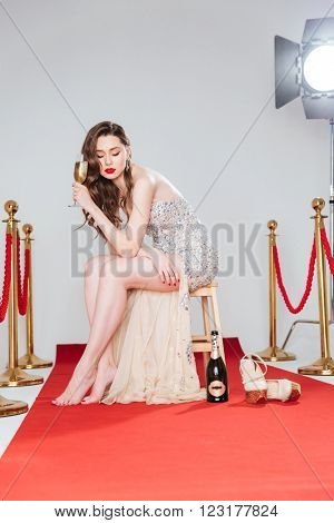 Beautiful woman holding glass with champagne on red carpet