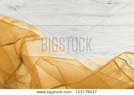 Crumpled yellow transparent chiffon on gray wooden background