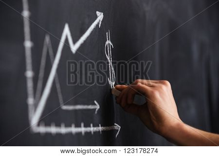 Increasing graph of currency rate drawn by hand on blackboard with chalk