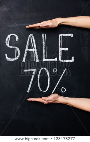 Two hands showing seventy percent sale drawn on blackboard with chalk