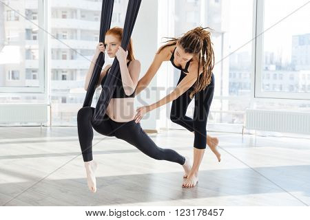 Concentrated young woman doing antigravity yoga using hammock with help of personal trainer