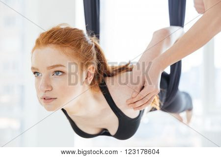 Beautiful redhead young woman doing pose of aerial yoga using hammock with personal trainer