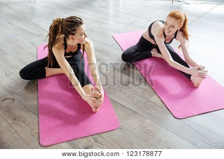 Two happy cute young women sitting and stretching in yoga center