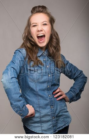 Portrait Of Energetic Fun Girl Student On A Gray Background In A Denim Jacket