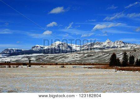 Breccia Cliffs and Breccia Peak on Togwotee Pass of the Absaroka Mountain Range during the winter in Wyoming USA with wispy cirrus and cumulus clouds over head