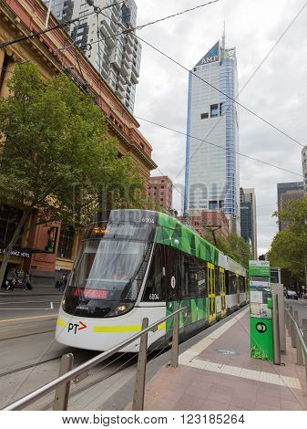 Melbourne - February 22 2016: The city tram stop in Melbourne at the tram stop and city skyscrapers February 22 2016 Melbourne Victoria Australia