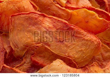 Macro closeup pile of thin sliced dehydrated orange papaya pieces
