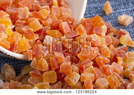 Closeup spilled bowl of dehydrated diced Carica papaya cubes on blue fabric placemat