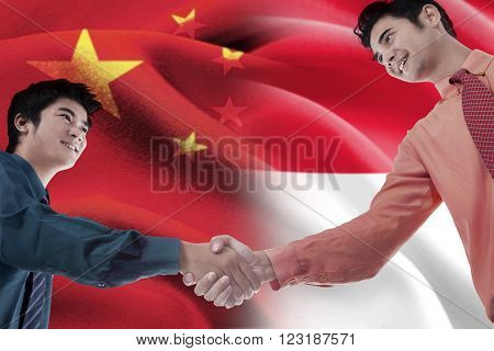 Portrait of young Chinese entrepreneur shaking hands with Indonesian person in front of Chinese and Indonesian flags