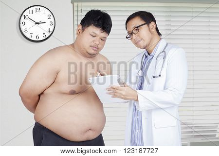 Photo of asian male doctor showing the test result on digital tablet to an overweight patient