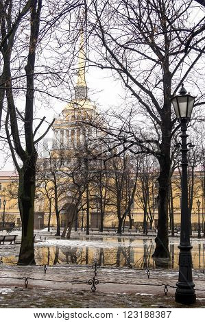 View of the Admiralty through the trees of the Alexander garden and the reflections in the puddles of classical architecture