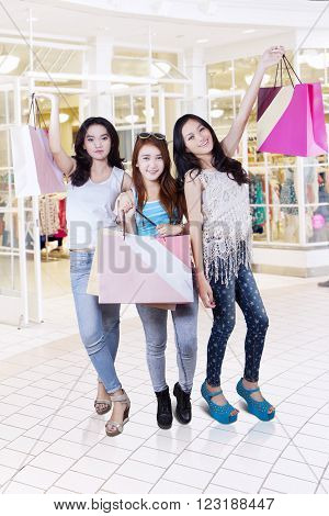 Portrait of beautiful teenage girls standing in the shopping center while holding shopping bags and looks happy