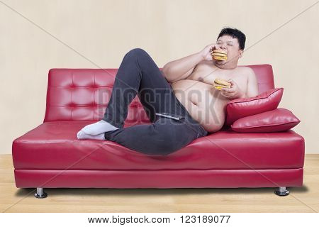 Picture of greedy person feels hungry and eat hamburger while leaning on the couch