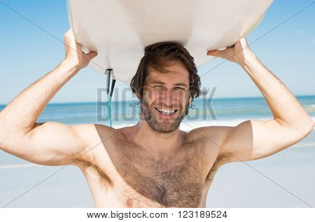Man carrying surfboard over his head. Close up face of handsome guy with surfboard on head at beach looking at camera. Portrait of latin man carrying surfboard on hid head and smiling at beach.