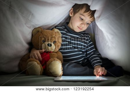 Cute little kid with his friend teddy bear using tablet computer under blanket at night in a dark room