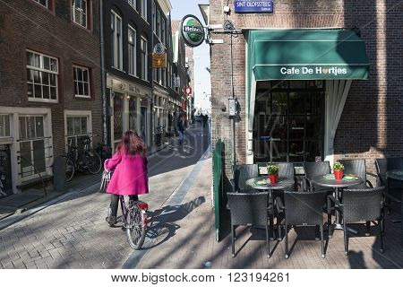 Amsterdam, Netherlands, 17 march 2016: girl in pink coat on bicycle in amsterdam red light district on sunny day near old bar