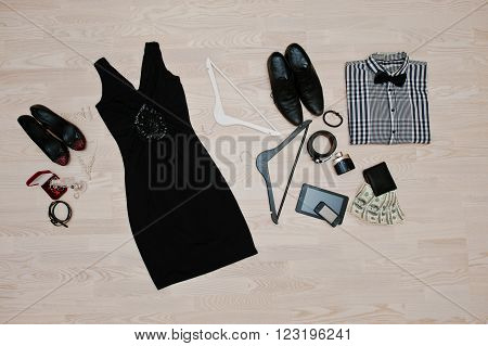 Set Of Trendy Clothes. Outfit Of Man And Woman Clothes And Accessories On Light Wooden Background