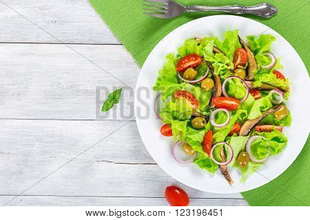 cherry tomatoes red onion green olives lettuce leaves smoked sprats