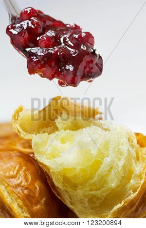 red cranberry jam on a spoon above a fresh croissant, vertical breakfast scene closeup with selected focus and narrow depth of field