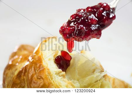 red cranberry jam on a spoon dripping on a fresh croissant, breackfast closeup shot with selected focus and narrow depth of field