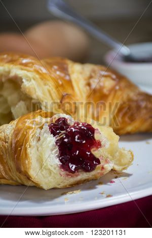 fresh croissant with red fruit jam for breakfast, closeup vertical selected focus and narrow depth of field